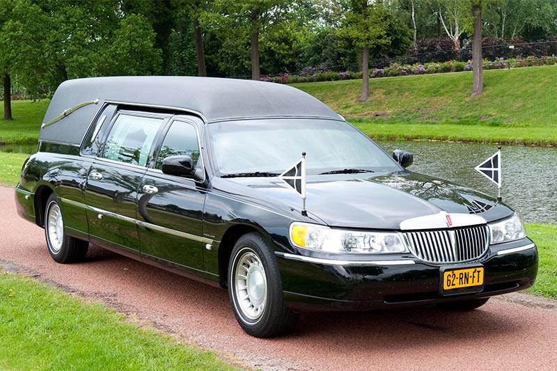 De traditionele, klassieke rouwauto, lijkwagen, lijkauto voor tijdens de uitvaart.